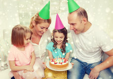 Família feliz com as duas crianças em chapéus do partido em casa Imagem de Stock Royalty Free