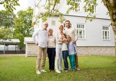 Família feliz na frente da casa fora Fotografia de Stock Royalty Free