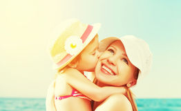Família feliz na praia filha do bebê que beija a mãe Fotografia de Stock