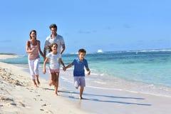 Família feliz nova que corre na praia que tem o divertimento Fotos de Stock