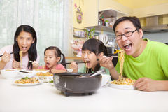 Família feliz que come macarronetes Fotografia de Stock