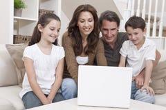 Família feliz que usa o computador portátil no sofá em casa Fotografia de Stock Royalty Free