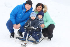 Família feliz & x28; pai, mãe, dois sons& x29; pose com snowracer Fotografia de Stock