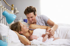 Família na cama que guarda a filha recém-nascida de sono do bebê Imagem de Stock