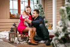 Família nova com um bebê que senta-se em um trenó em decorações do Natal Foto de Stock