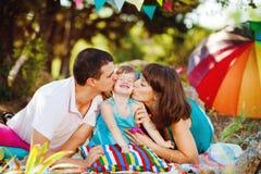 Família nova feliz com a criança que descansa fora no parque do verão Fotos de Stock Royalty Free