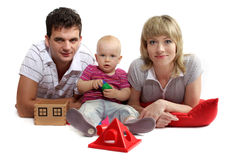 Família nova feliz que encontra-se no assoalho em coxins vermelhos Imagens de Stock