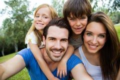 Família nova feliz que toma selfies com seu smartphone na paridade Imagem de Stock Royalty Free