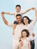 A família nova feliz tem o divertimento na praia Imagem de Stock