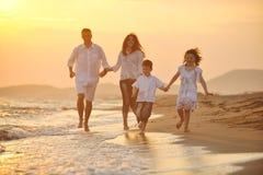A família nova feliz tem o divertimento na praia Foto de Stock