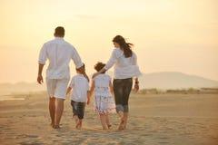 A família nova feliz tem o divertimento na praia no por do sol Imagem de Stock Royalty Free