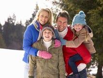 Família nova na cena alpina da neve Imagens de Stock