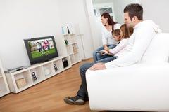 Família nova que presta atenção à tevê em casa Fotos de Stock Royalty Free