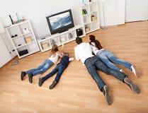 Família nova que presta atenção à tevê em casa Fotografia de Stock Royalty Free