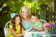 Família nova que senta-se na tabela no jardim Imagem de Stock Royalty Free