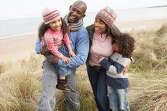 Família que anda ao longo das dunas na praia do inverno Fotografia de Stock