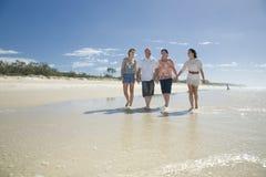 Família que anda nas mãos da terra arrendada da praia Imagem de Stock Royalty Free