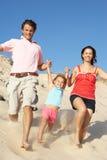Família que aprecia o feriado da praia que funciona abaixo da duna Fotografia de Stock Royalty Free