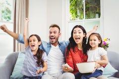Família que cheering ao olhar a tevê em casa Fotos de Stock