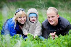 Família que coloca na grama Imagens de Stock Royalty Free