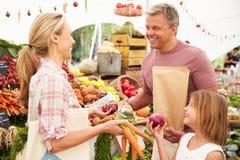 Família que compra legumes frescos na tenda do mercado dos fazendeiros Imagem de Stock