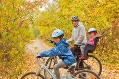 Família que dá um ciclo ao ar livre, outono dourado no parque Imagens de Stock