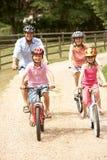 Família que dá um ciclo na segurança desgastando Helme do campo Fotos de Stock Royalty Free