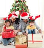 Família que decora uma árvore de Natal Fotos de Stock