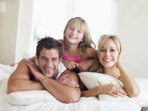 Família que encontra-se no sorriso da cama Imagens de Stock Royalty Free
