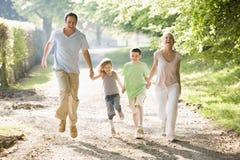 Família que funciona ao ar livre prender as mãos e sorrir Fotos de Stock Royalty Free