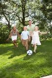 Família que joga o futebol no jardim Fotos de Stock