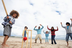 Família que joga o grilo na praia Fotografia de Stock Royalty Free