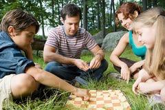 Família que joga verificadores Fotografia de Stock