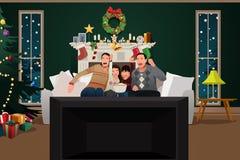 Família que olha a tevê durante a estação do Natal Imagem de Stock