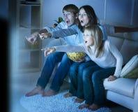 Família que presta atenção à tevê Fotos de Stock Royalty Free