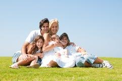 Família que senta-se em uma grama Foto de Stock Royalty Free