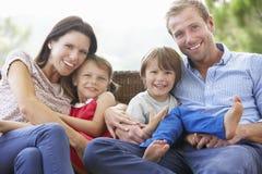Família que senta-se no jardim Seat junto Imagens de Stock Royalty Free
