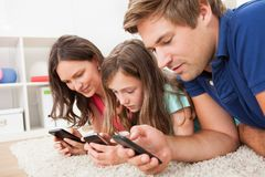 Família que usa telefones espertos em casa Fotos de Stock Royalty Free
