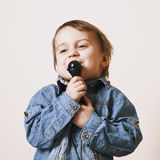 The famous actress. Humorous photo baby girl singing with a micr. Ophone creativity, development, music, success concept Stock Photos