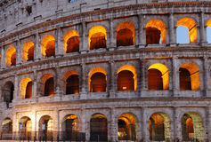 The famous ancient Roman Colosseum structure illuminated during dusk Stock Photo