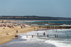 Famous beach on the ocean where sunbathing and resting a lot of people, Lisbon, Portugal stock photos