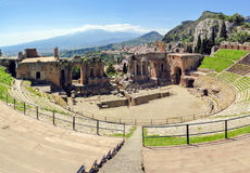 The famous and beautiful ancient greek theatre ruins Taormina with Etna volcano in the distance. Outdoor shot, Sicily, Italy Royalty Free Stock Photo