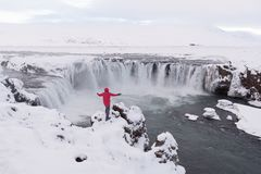 Famous and beautiful Icelandic waterfall Godafoss north iceland.Tourist photographer in red jacket standing at Godafoss powerful