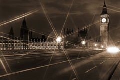 Famous and Beautiful night view to Big Ben and Houses of Parliam. Ent from Westminster Bridge  through nigh lamp rays, London, UK Royalty Free Stock Image