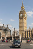 Famous black cab driving by Houses of Parliament Stock Photos