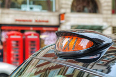 Famous black cab on a street in London. Famous taxi cab (hackney) on a street in London, UK Royalty Free Stock Photos