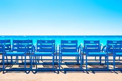 Famous blue chairs on the Promenade des Anglais in Nice, France. Beautiful turquoise sea and beach royalty free stock image