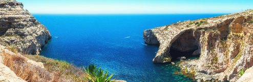 Famous Blue Grotto in Malta. Near Zurrieq on a calm sunny day. Horizontal panorama from 5 vertical frames Royalty Free Stock Photos