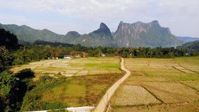Blue lagoon, Vang vieng, Laos. flying over rice fields on the background of high mountains and hills stock video footage