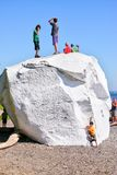 Famous Boulder at White Rock beach, British Columbia, Canada. WHITE ROCK, CANADA - JULY 23, 2010: Kids climbing on top of the famous boulder at the coastal city Royalty Free Stock Photo